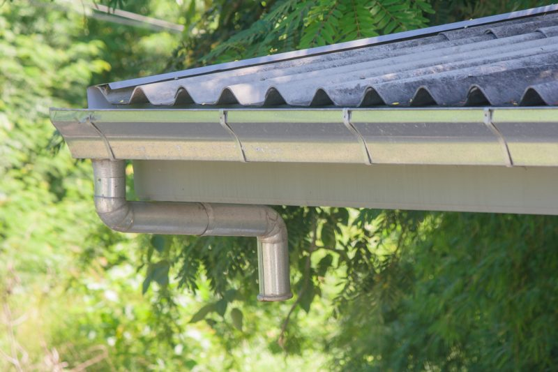 Stainless rain gutter on roof of wooden house with sunlight background.